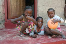 Tre barn leker med ball på gulvet.