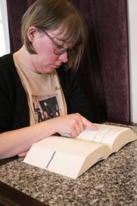 Dame 34 år sitter ved et bord og leser fra en bok.