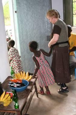 En liten jente holder en dame i hånden og titter nysgjerrig ut av en dør.