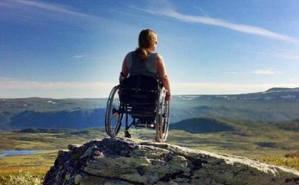 Ung dame i rullestol på en fjelltopp. Sitter med ryggen til.