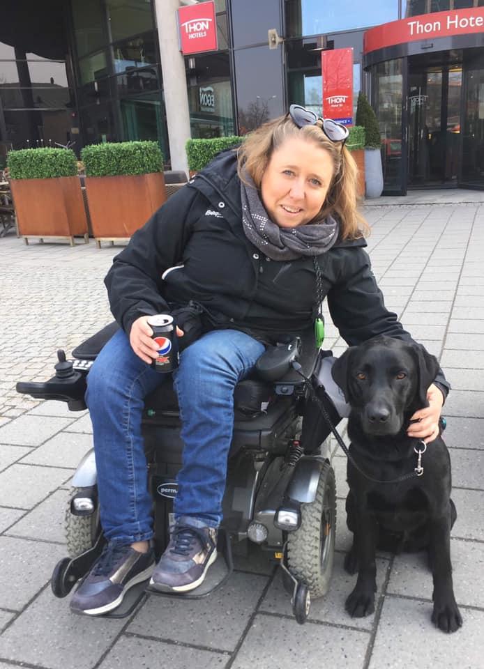 Smilende dame i rullestol klapper sin servicehund.