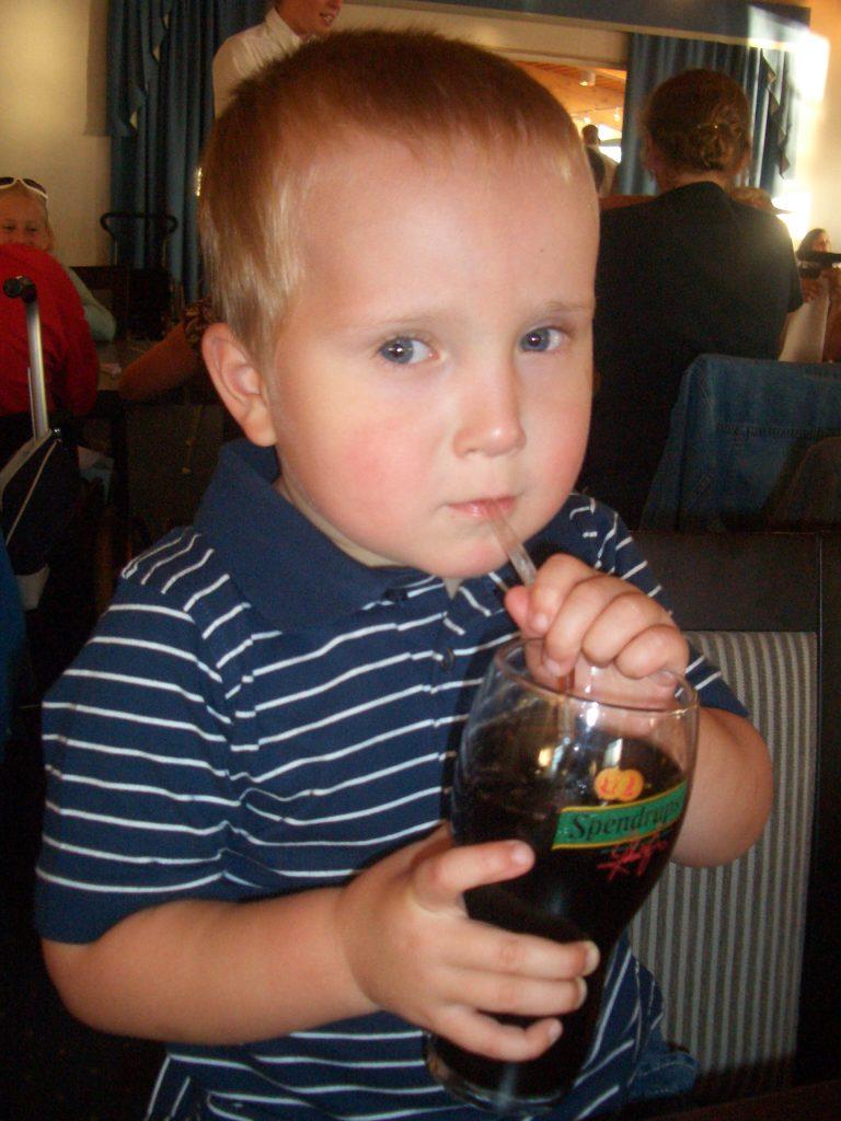 Gutt 4år drikker cola av et stort glass med sugerør.