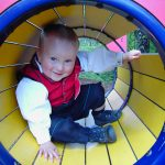Smilende gutt 3år i bunad inne i klatrestaiv.