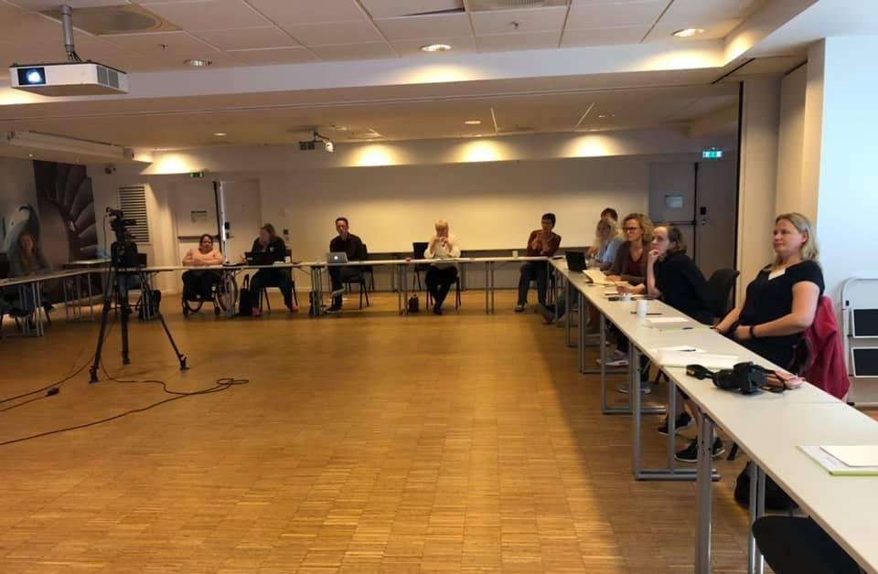 Deltakerne i storstyremøtet sittende bak konferansebord i U-form.