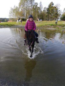 En ung jente smilende på hesteryggen.