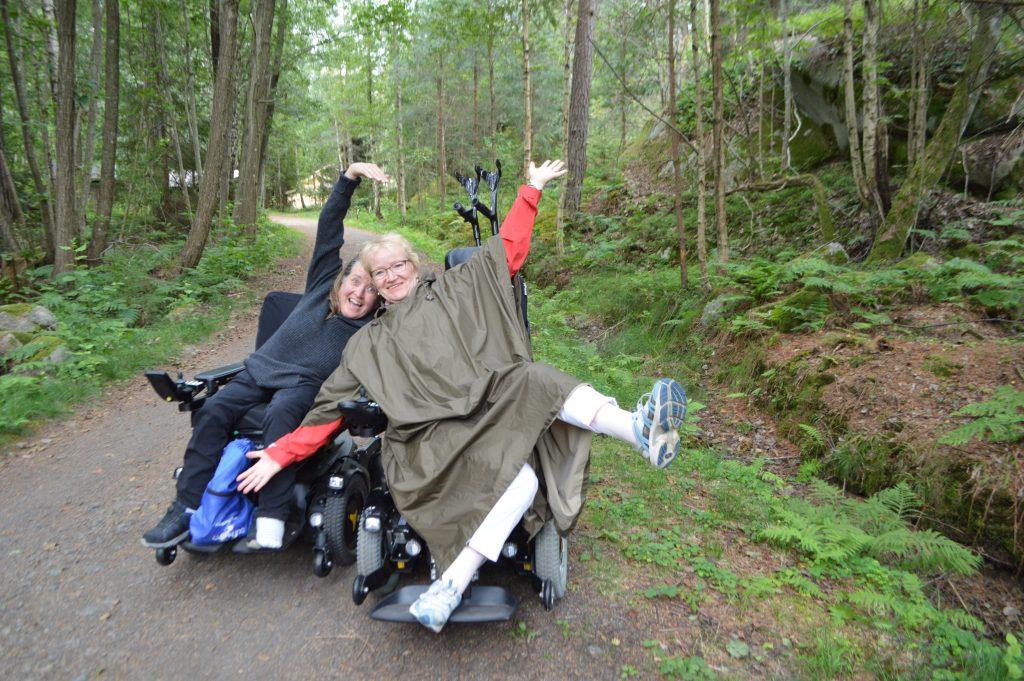 To glade damer tøyser i rullestolene sine.