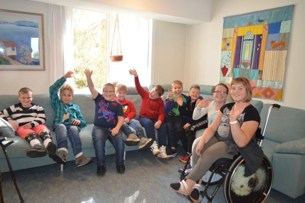 En gjeng med glade barn som sitter i en sofa og vinker.