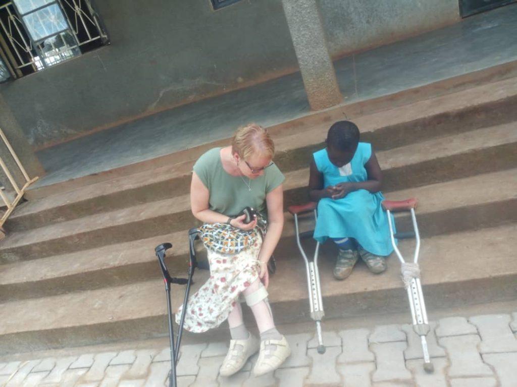 Dame med krykker viser frem sine skinner til et barn med krykker.