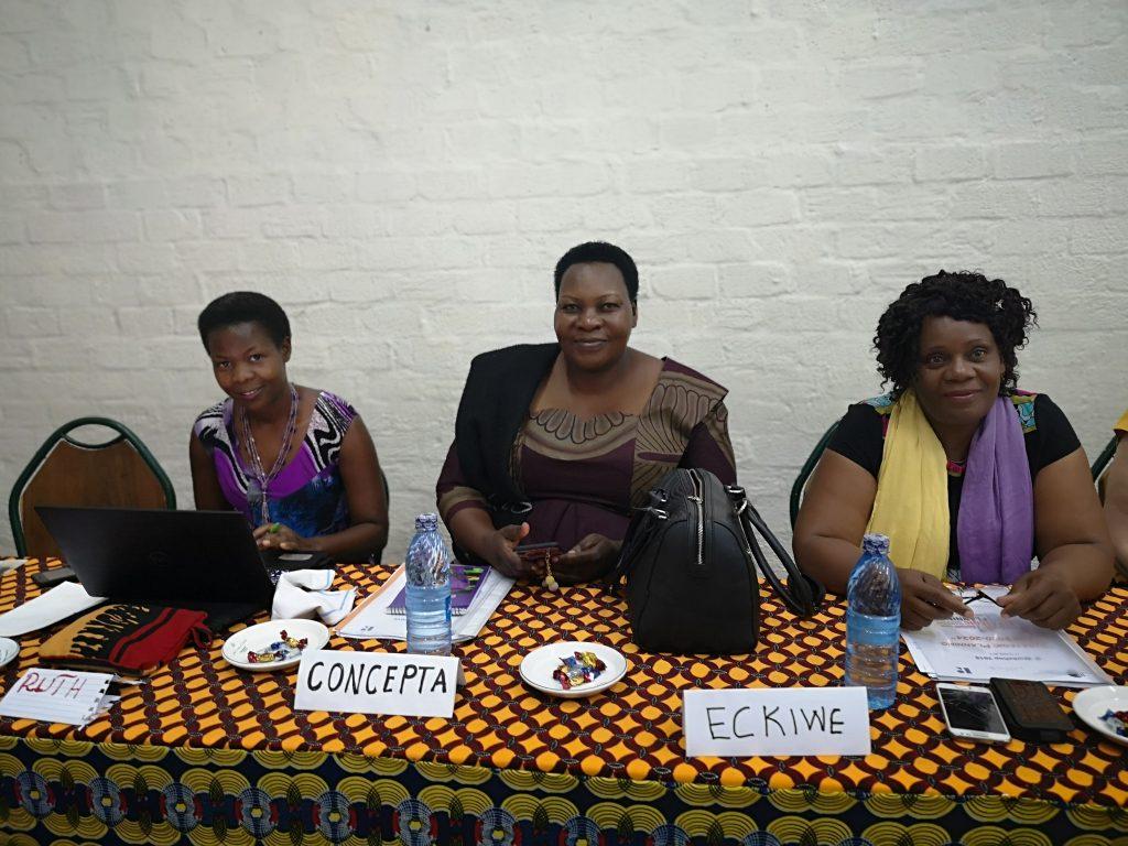 Tre afrikanske damer sittende bak et bord.