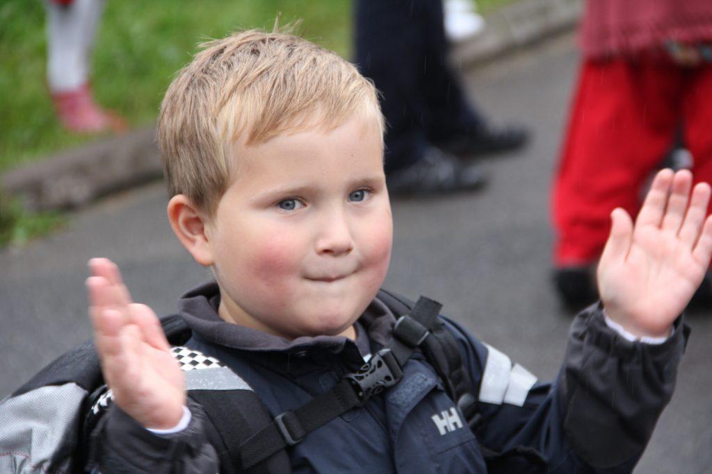 Gutt 6år klapper med skolesekk på ryggen.