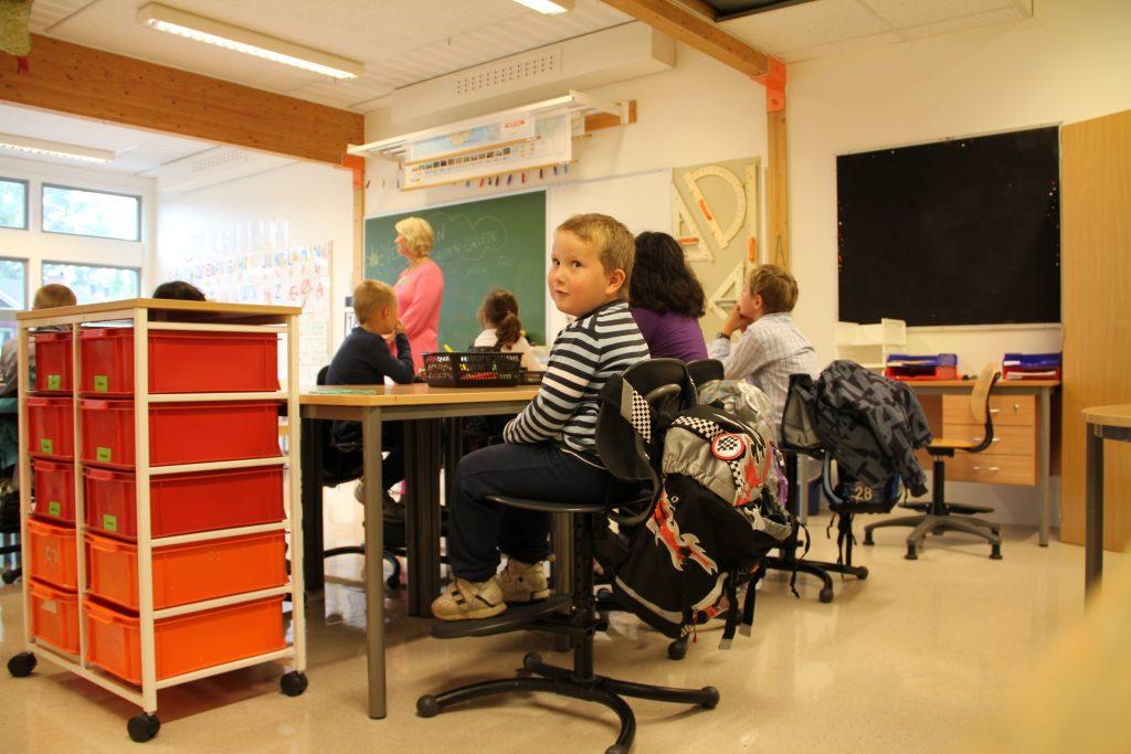 Gutt 6år sitter spent ved pulten første skoledag.