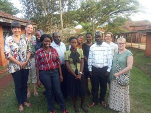 11 personer stående på gressplen i Uganda.