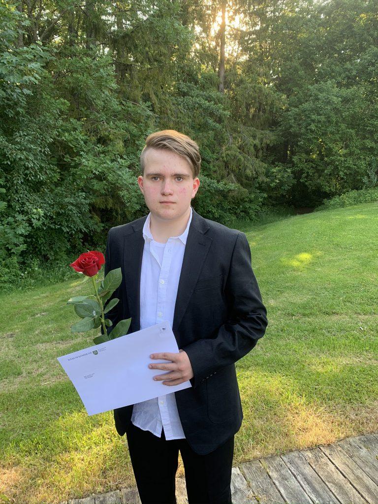 Gutt 16år med dress og rød rose hånden.