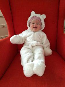 En jentebaby smiler i hvit bamsedress. Sitter i en rød lenestol.