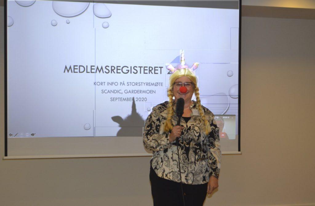En blid dame med blond parykk, enhjøringhorn og rød klovnenese foran lerret med skrift medlemsregisteret.