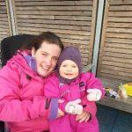 Elisabeth som sitter i rullestol sammen med sin lille datter. Begge i knall rosa utetøy