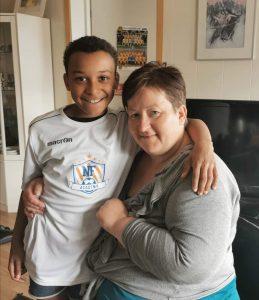 Mamma renate som sitter og sønnen Levi står og holder armen over skuldrene hennes