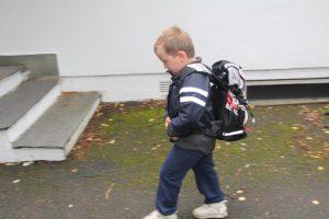 Gutt 6år på vei til første skoledag med skolesekk på ryggen.