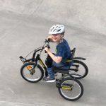 Ung gutt på sykkel hjelpemotor og ett hjul foran og to bak