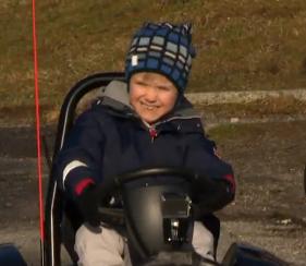 Liten gutt i en elektrisk firhjuling.