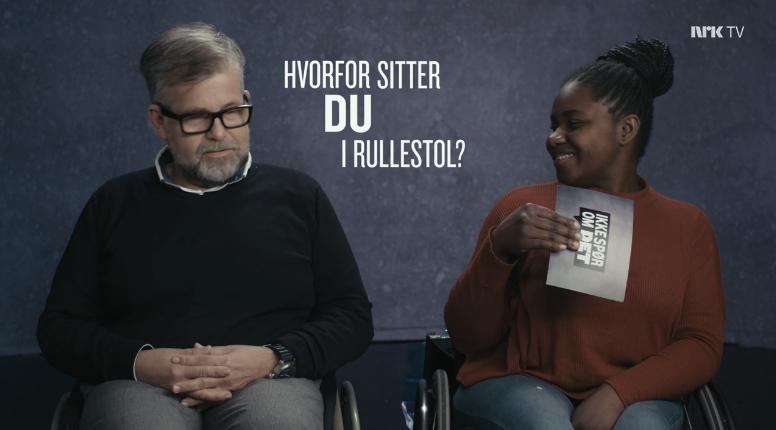 En mann og en dame i rullestol sitter ved siden hverandre og spør hverandre spørsmål fra et kort