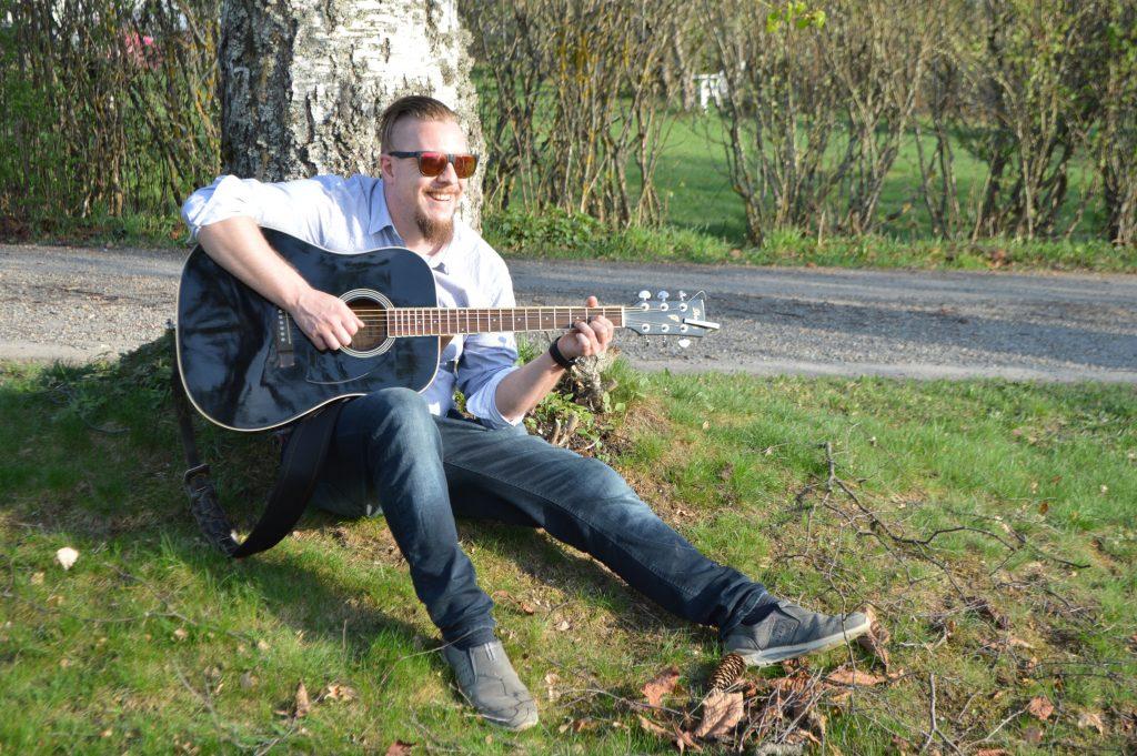 Ung mann sitter å spiller gitar under et tre.