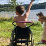 Gutt i rullestol sett bakfra strekker en arm i været.