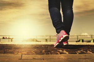 En person går på asfalt mot soloppgagen. Man ser kun to rosa jobbesko og nedre del av bena