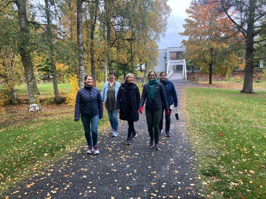 Fem glade damer på tur i parken.
