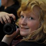 Smilende ung jente med fotoapparat.