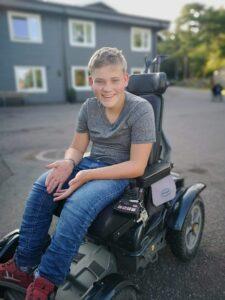 Tenåringsgutt med lyst hår, grå t-skjorte og jeans sitter i sin elektriske rullestol