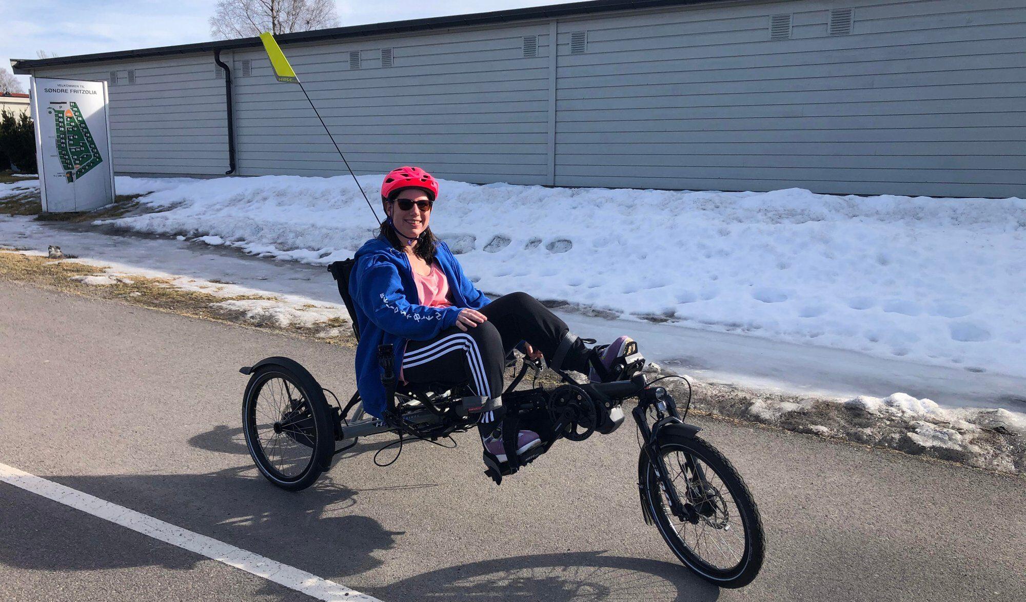 Smilende dame på trehjuls sittesykkel.