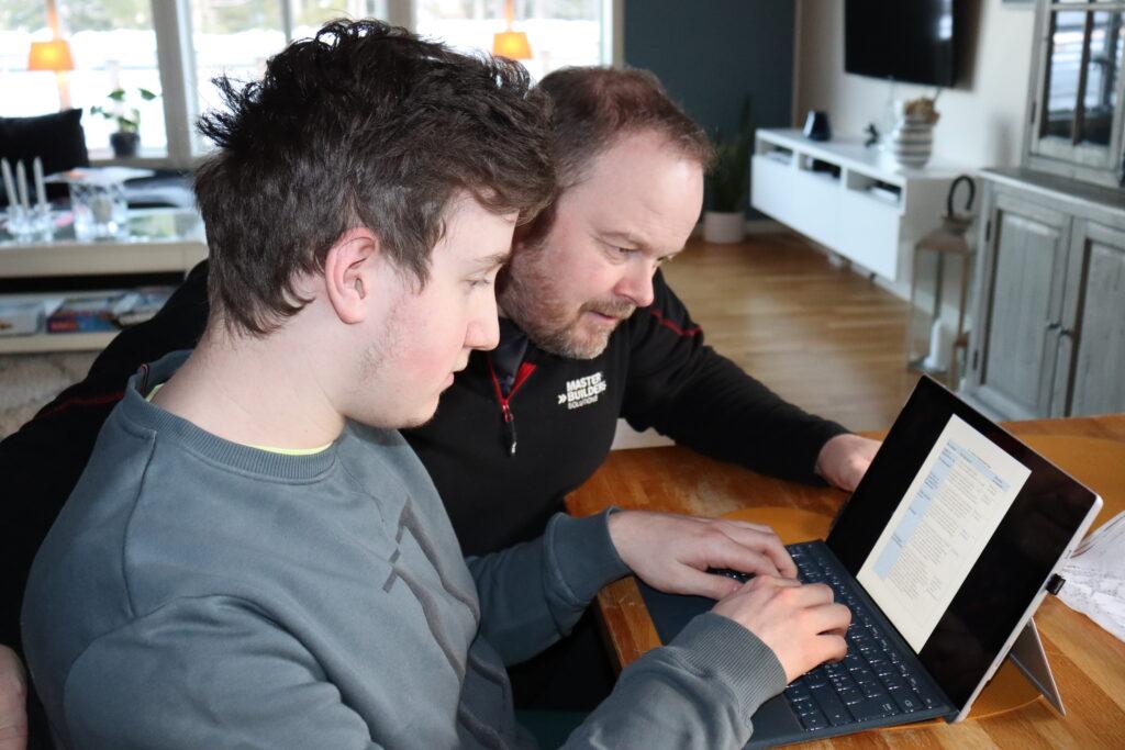 Sander og pappa Tor Andre sitter foran en bærbar PC og ser på Sander sin individuelle plan