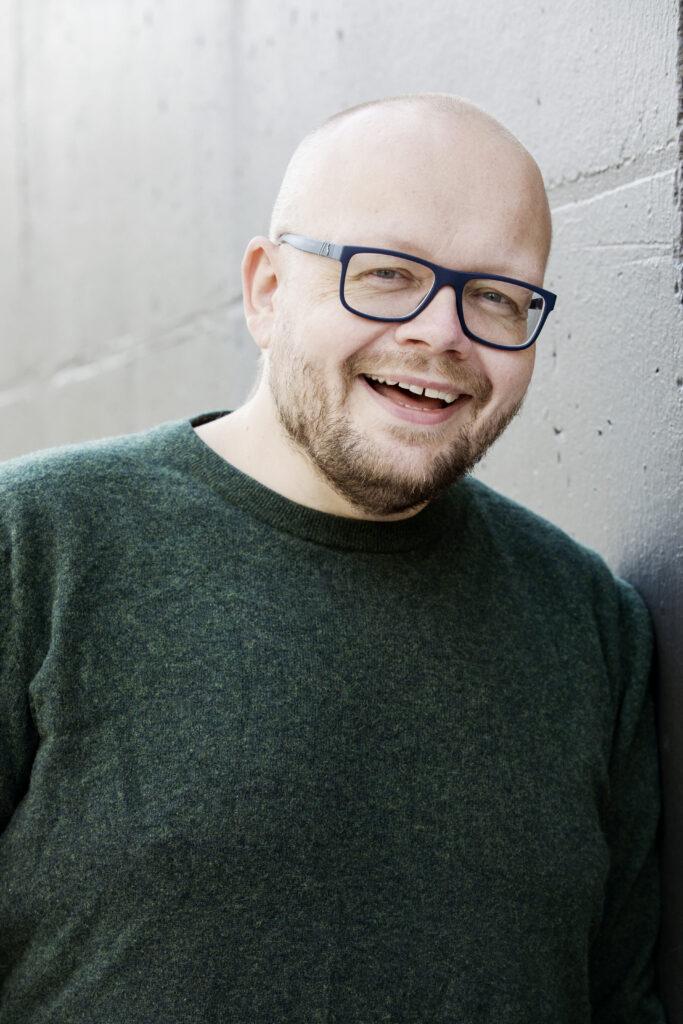 Bjørn, mann med mørk genser og briller smiler mot kamera.
