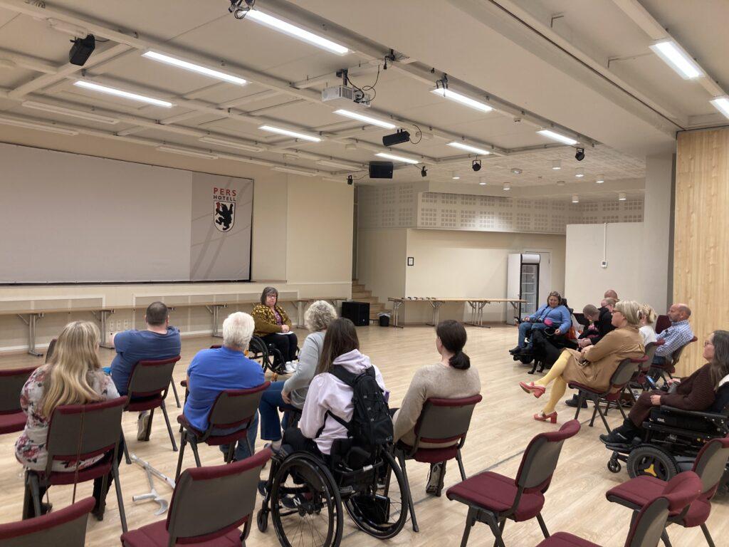 Kvinne i rullestol holder foredrag foran en forsamling på Pers Hotell på Gol.