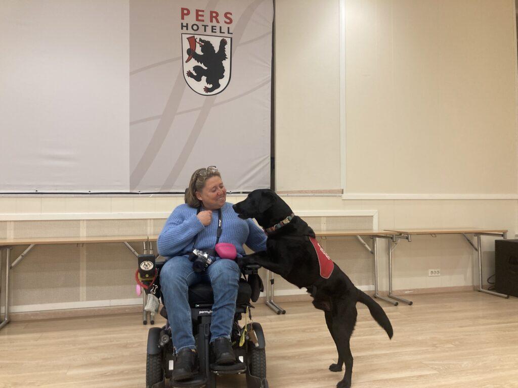 Kvinne i elektrisk rullestol med svart servicehund stående med forlabbene på hennes fang.