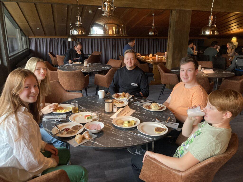 Unge medlemmer i RHØst sitter å spiser rundt et rundt bord i restauranten på Pers Hotell på Gol.