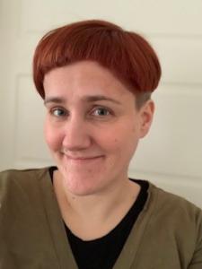 Kvinne med kort, rødt hår og grønn genser smiler mot kamera